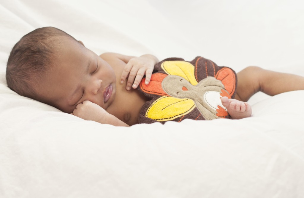 Newborn Photography by Liz Davenport Creative of a baby on white sheet holding a turkey bib